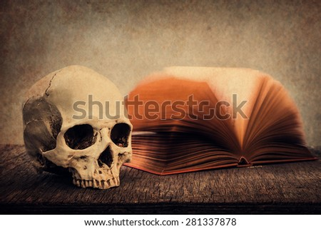 Still life with skull and old book on wooden table over grunge background - stock photo