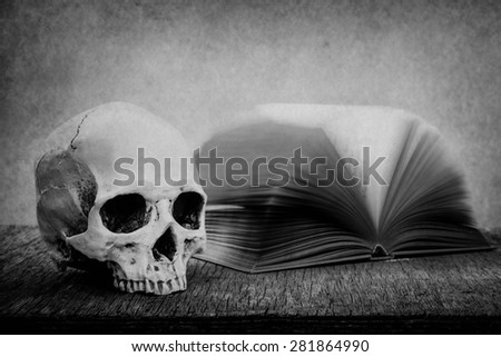 Still life with skull and old book on wooden table over grunge background, black and white - stock photo