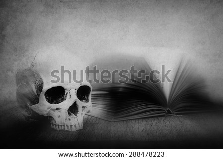 Still life with skull and old book on wooden table over grunge background, black and white