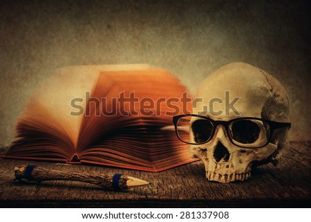 Still life with skull, old book and pencil on wooden table over grunge background - stock photo