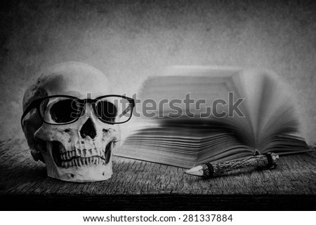 Still life with skull, old book and pencil on wooden table over grunge background, black and white