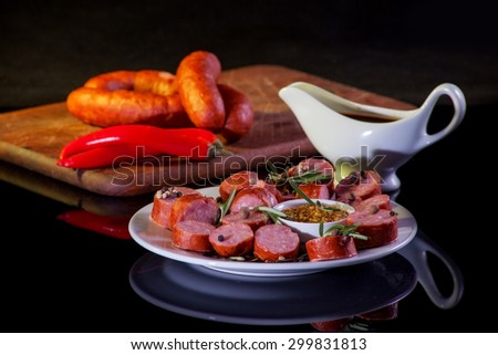 still life with sliced sausage, pepper, rosemary, sauce and mustard. on black background