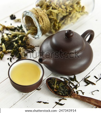 Still life with small cup of green tea, brown tea pot and spoon full of raw tea leaves, chinese tea concept - stock photo