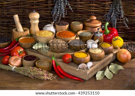 still life with spices and herbs in wooden bowl on wooden table - stock photo