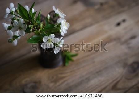 still life with spring blossoms in vase on wooden surface - stock photo