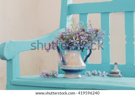 still life with spring flowers on blue bench - stock photo