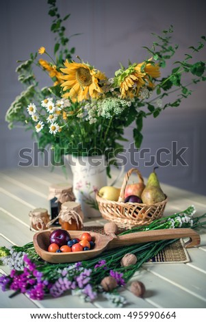 Still life with sunflowers, wildflowers, blueberry jam, pears, apples, plums and walnuts