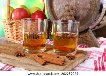 Still life with tasty apple cider and fresh apples, on nature background - stock photo