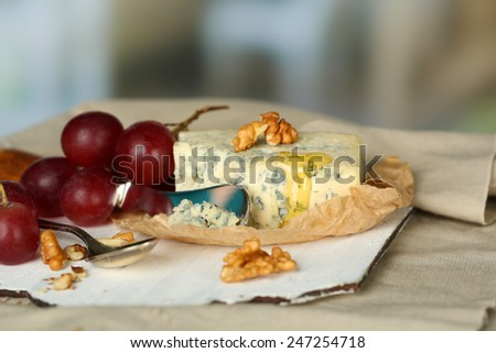 Still life with tasty blue cheese on table, on light background