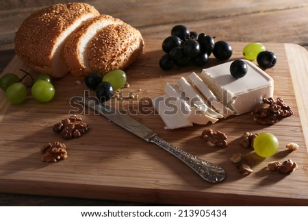 still life with tasty cheese, grape and bread, close up - stock photo