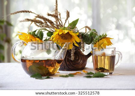 Still-life with tea in a transparent teapot and a bouquet of sunflowers in a ceramic vase