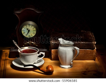Still life with tea, old books, milk jug, pipe and clock - stock photo