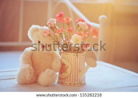 Still life with teddy bear and pink flowers in the watering can with back light - stock photo