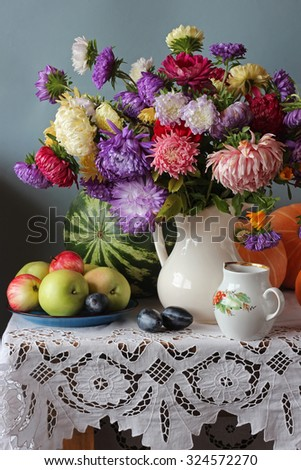 Still life with the bouquet of asters, plums, pumpkins and  a water-melon located on a table on a white cloth with laces against a blue wall. - stock photo