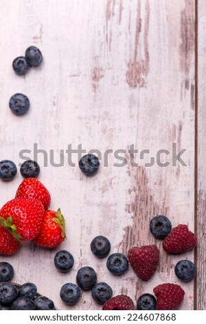 Still life with the tempting raspberry lying near the scattering blackberry and red delicious strawberry on the wooden table. Top view - stock photo