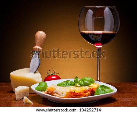 still life with traditional lasagna, red wine and cheese - stock photo