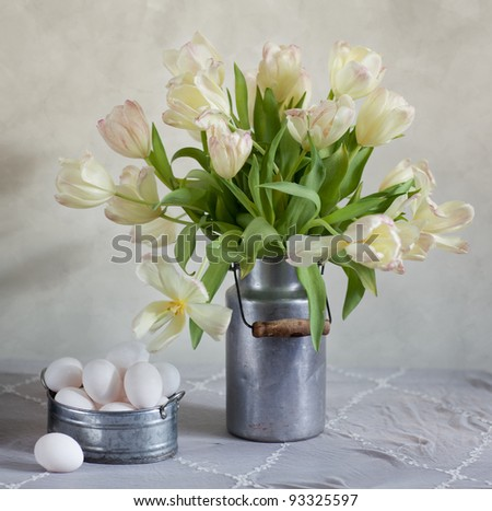 Still Life with Tulips in old milk can and eggs - stock photo