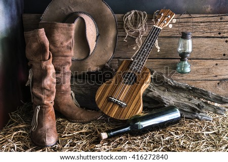 Still life with ukulele on american west rodeo brown felt cowboy hat and traditional leather boots in vintage ranch barn background - stock photo