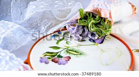 Still life with unfinished embroidery, threads and lace - stock photo