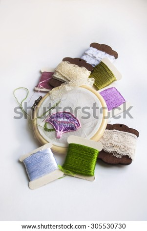 Still life with unfinished silk embroidery, threads and lace - stock photo