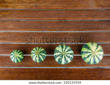 Still life with variety of green pumpkins cucurbita pepo arranged in a row on wooden table with a copyspace, useable as seasonal autumn harvest Halloween housing decoration illustration - stock photo