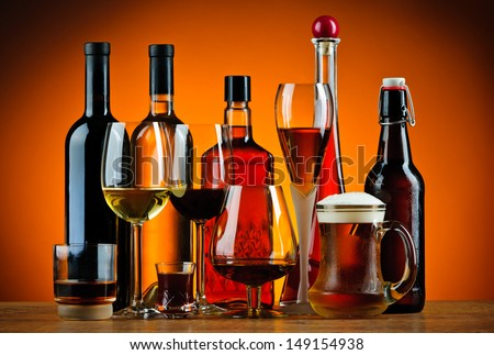 still life with various glasses and bottles of alcohol - stock photo