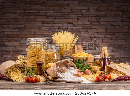 Still life with various traditional italian pasta and ingredients  - stock photo