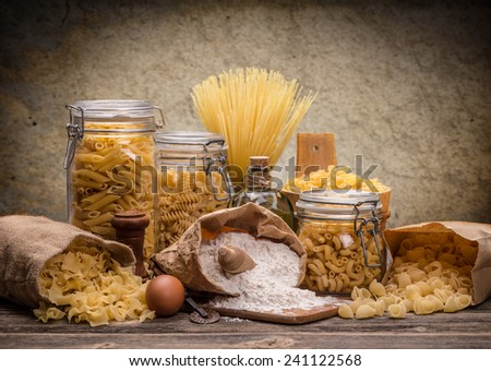 Still life with various traditional italian pasta on rustic wooden board - stock photo