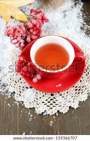 Still life with viburnum  tea in cup, berries and snow, on  wooden background