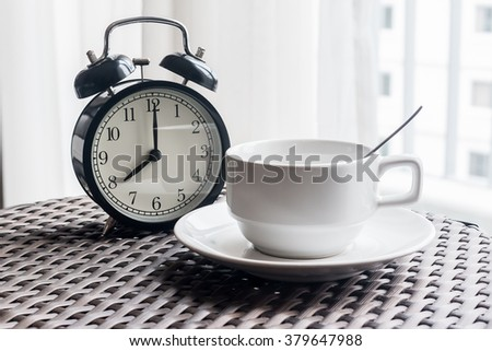 Still life with vintage alarm clock and coffee cup on weave table ( alarm clock show 8 o`clock ) - stock photo