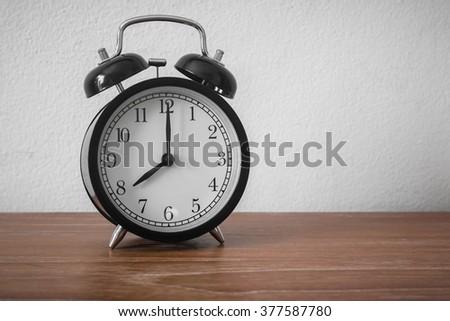 Still life with vintage alarm clock on wood table ( alarm clock show 8 o`clock ) - stock photo