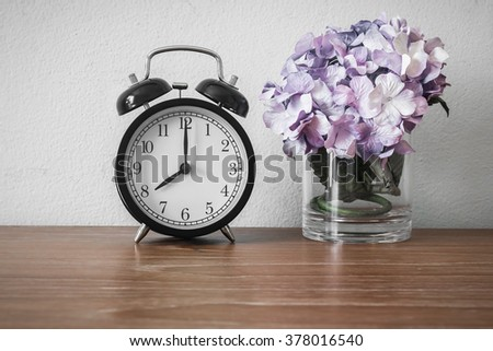 Still life with vintage alarm clock with flower on wood table ( alarm clock show 8 o`clock ) - stock photo