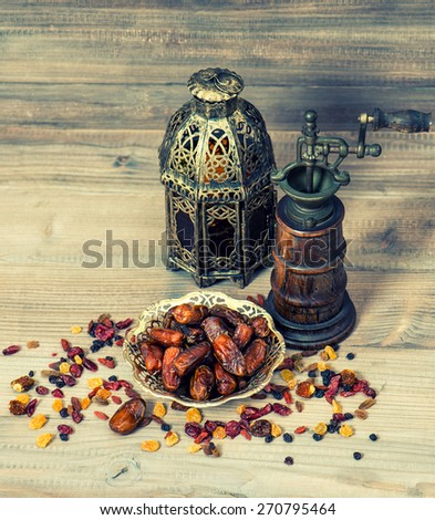 Still life with vintage oriental lantern and mill. Raisins and dates on wooden background. Creative food - stock photo
