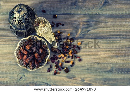 Still life with vintage orintal lantern, raisins and dates on wooden background. Retro style toned picture - stock photo