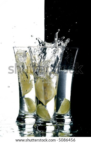 still life with water and lemon on the white background - stock photo