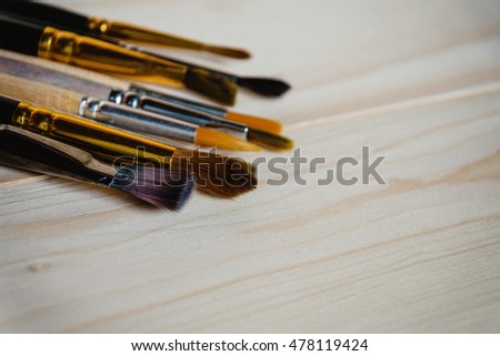 Still life with watercolor brushes on a wooden background