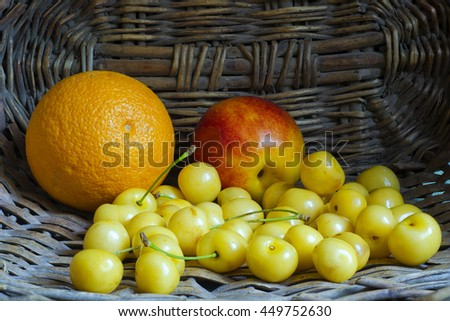Still life with white cherry, orange and peach. Fruits are in wicker basket.