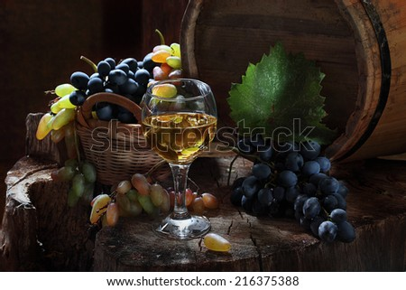Still-life with white wine and juicy grapes, fragrant white wine and clusters of ripe sweet juicy dark blue and pink grapes - stock photo
