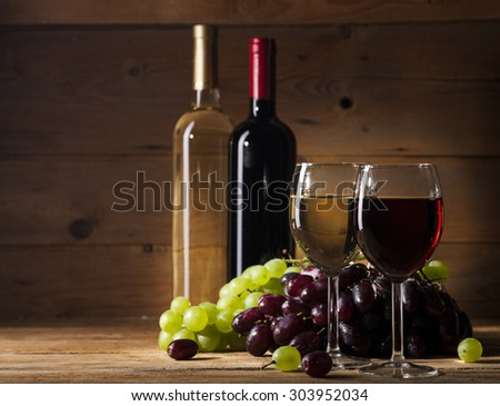 Still life with wine and bunch of grapes on old wooden background