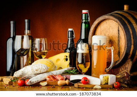 still life with wine, beer, traditional food, cheese and sausages - stock photo