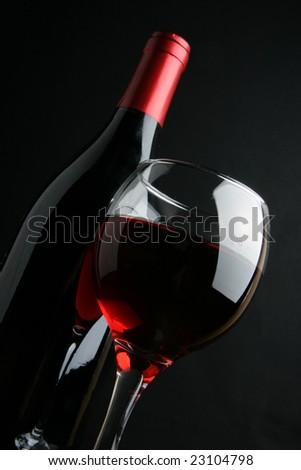 Still-life with wine bottle and glass over black background - stock photo