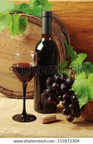 Still life with wine bottles, one glass of red wine, grapes  and oak barrel