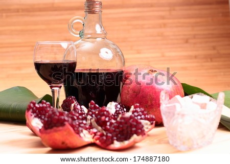 Still-life with wine, garnet and sweets on the wood table - stock photo
