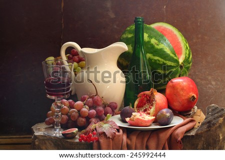 Still-life with wine, grapes, a pomegranate, a fig, a water-melon and a white jug - stock photo
