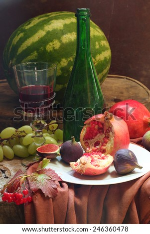 Still-life with wine, grapes, a pomegranate, a fig and a water-melon  - stock photo