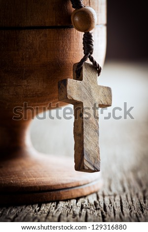 still life with wooden cross and wooden chalice - stock photo