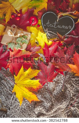 Still life with wrapped gift, colorful dry leaves, small red apples and autumn inscription - stock photo