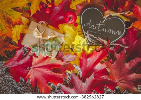 Still life with wrapped gift, colorful dry leaves, small red apples and autumn inscription
