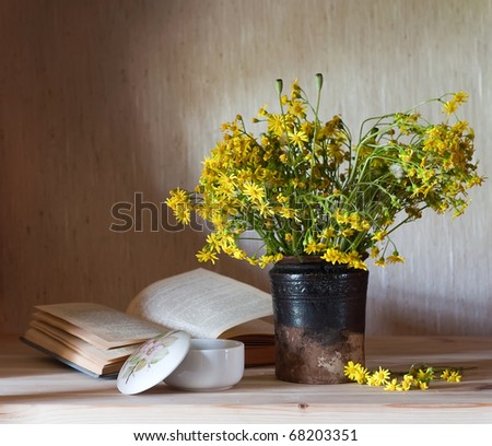 still life with yellow flowers and booc