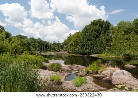 Still river with green forest banks and stones, white clouds - stock photo